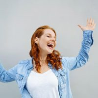 Laughing carefree young redhead woman raising her arms in the air and dancing with happiness and joy over a light grey background